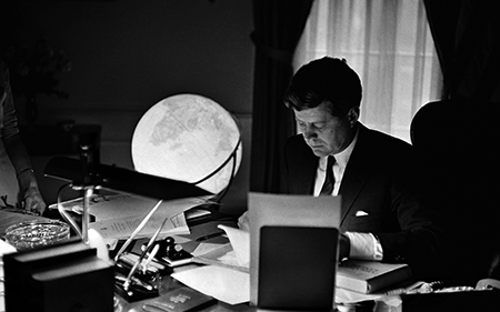 Photos of JFK at his desk, at the signing of a 1963 Farm Bill, and during a moment of smilingly engaging an audience.